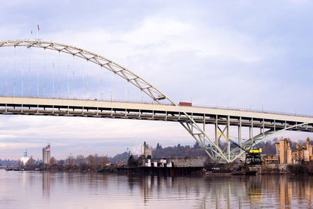Spectacular original unique arched Fremont bridge across the Willamette River in the city bridges Portland Oregon in a quiet calm weather with reflection in water and cloudy sky.