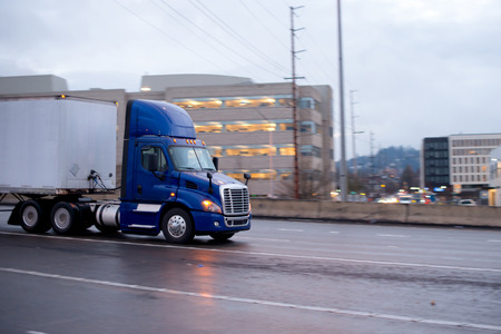 freightliner: Large blue bonneted big rig semi truck with headlight turn on and dry van trailers for commercial cargo going by highway a urban city with high-rise multi-levels buildings in the wet rainy weather day Stock Photo