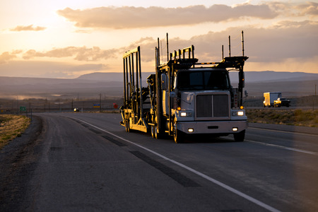 애리조나 황혼의 직선 도로에서 트레일러 선반에서 태양의 마지막 광선과 함께 차량을 운송하기위한 자동차 운송업자 트레일러가있는 큰 리그의 강력 스톡 콘텐츠