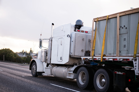 slings: King of American roads - a powerful heavy semi truck with a spacious cabin designed for both work and leisure, transports on a flat bed trailer commercial freight, secured on the trailer with slings, moving on a flat straight and wide freeway