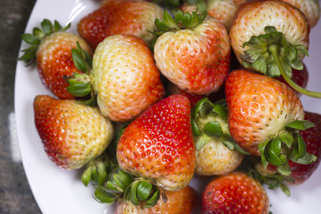Fresh unripe appetizing strawberries with bright green tails laid out on the plate as a fruit vitamin dessert for lovers of healthy food Stock Photo