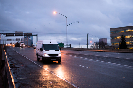 The compact van for the transport of commercial goods and parcels, as well as for use in a small business, traveling on the evening road with turn on headlights in the twilight reflecting light on the wet rain highway Stock Photo
