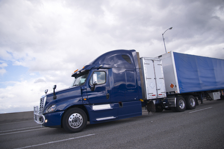 Modern mainline industrial dark blue semi truck for long distance transport with an additional container for storing the equipment and tools, and trailer covered with blue waterproof fabric moving on the highway