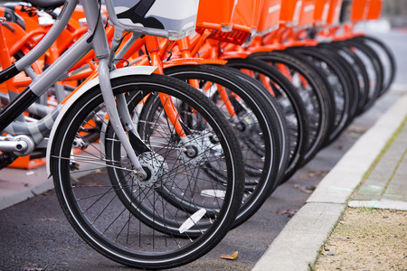 Orange bikes with baskets in front and polished wheels for paid public use stay lined and one gray bike symbolic not likely other stand out from the rest of this series