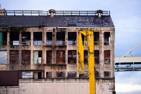 eye socket: Old abandoned industrial dilapidated high-rise building with broken windows, reminiscent of the empty eye socket, and arrow construction crane, ready to complete the demolition of this old building