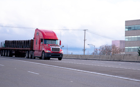 Red big rig American long haul semi truck with a long flat bed trailer delivering metal wire cargo on multi-lines highway