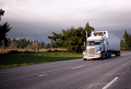 streight: Big Rig classic semi truck with reefer unit on refrigerator trailer for transporting food cargo moving wide streight highway in sunshine day with trees and green grass on roadside