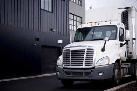 transport truck: Middle size rig white semi truck with reefer unit on refrigerator trailer unload on warehouse parking lot with warehouse buildings painted in grey Stock Photo