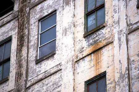 inoperative: The outer wall of the old inoperative derelict abandoned multi-storey industrial building from painted bricks with rows of windows and rusted metal parts and exfoliated paint Stock Photo