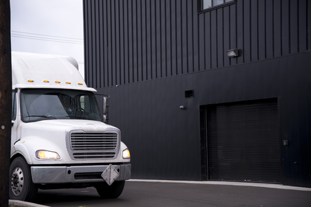 White middle-class semi truck day cab with trailer for transport of explosive and flammable substances is standing near a warehouse in anticipation of unloading the delivered load Stock Photo