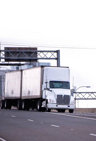 Professional powerful American big rig semi truck for long-distance transport of commercial goods by road between states, pulling dry van tandem trailers with a heavy load and an additional axis for even weight distribution