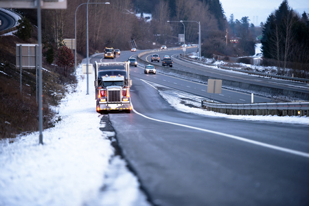perishable: A large classic big rig semi-truck with a refrigerated trailer for the transportation of perishable goods over long distances along the highways of America stands on the side of the road in the snow-covered winter at state of Washington. Stock Photo