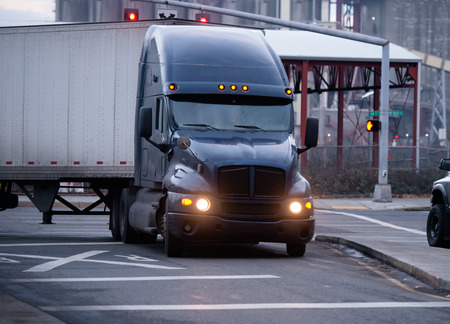 free image: A large classic dark big rig semi-truck with a turn on headlights and dry van trailer for the transportation of commercial goods over long distances along the highways of America turn on the side of the road with traffic lights and railroad