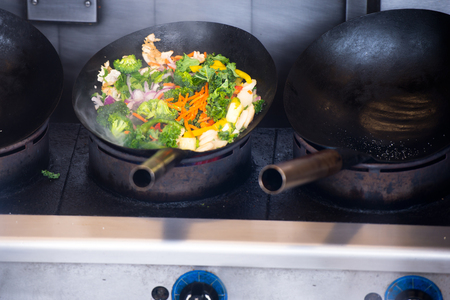 browned: Sliced vegetables from cabbage, broccoli, carrots, onions and zucchini stew in a large sooty industrial frying pan on a three-plank stove - healthy food - the success of longevity and health