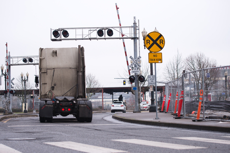 restrictive: A dirty semi truck tractor without a trailer crosses an open railroad crossing with warning signs and traffic lights along the road with construction restrictive cones along one side and a pedestrian crossing lines.