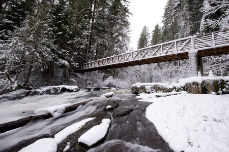 An elegant narrow pedestrian bridge with high rails through a mountain stream in a wild, snow-covered quiet forest is an excellent place for healthy walks on the fresh air Stock Photo