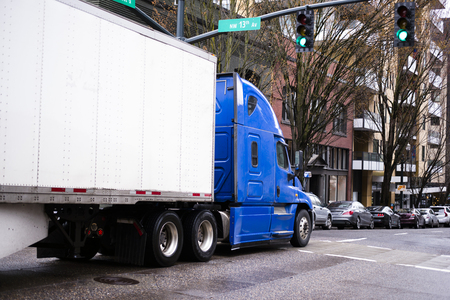 building color: Modern pro big rig semi truck in blue color with dry van trailer moving by urban city street with modern building and cars passing greel traffic light Stock Photo