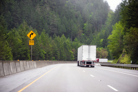 Big rigs Semi-Trucks with semi trailers moving in both directions along a wide highway with divided lanes, passing in the midst of wooded by evergreen trees hills and a yellow traffic sign with arrow