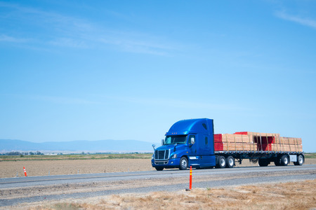 A blue modern big rig semi truck with a high cabin and a flat bad trailer carries stacks of boards reinforced with slings along the road with separated lanes in the opposite traffic direction. Banco de Imagens - 80406385