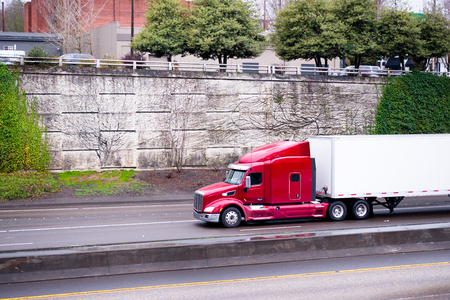 A profile of a huge red American big rig semi truck with a raised cab with spoiler for the drivers rest during the transportation of goods in a dry van trailer for long haul moves along a highway with a high stone wall entwined by green ivy