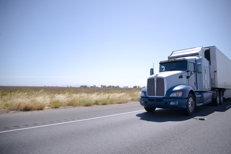 Big powerful custom built big rig semi truck with refrigerated trailer transports perishable goods that require storage at low temperature, on straight road in California Foto de archivo