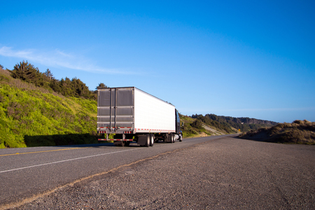 Alone semi truck with a dry van trailer leaves into the distance beyond the horizon line on a lonely road with green grass and bushes along the Pacific coast in the Northwest