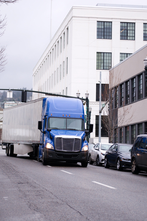 freightliner: A blue modern semi truck with high roof to reduce air resistance and improve aerodynamics carries dry van trailer with cargo along the road in an urban city street