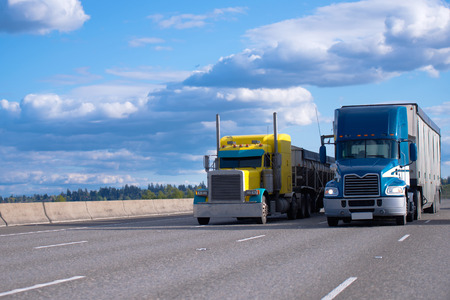 Two semi trucks of various models and manufacturers, a yellow classic American semi truck with a bulk trailer and a blue modern American semi truck with a high trailer for bulk cargo rushing along a wide highway next to each other