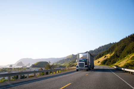 Spectacular landscaping with big rig semi truck and trailer which moving by empty highway along the Pacific coast with big cliffs in ocean waves and among the green hills on another side