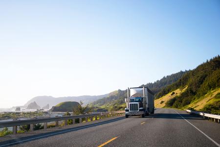 Espectacular paisajismo con gran camión semi plataforma y remolque que se mueve por una carretera vacía a lo largo de la costa del Pacífico con grandes acantilados en las olas del océano y entre las verdes colinas en el otro lado