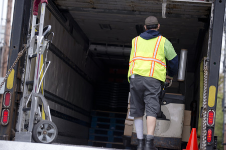 The truck driver in safety bright vest unloads the goods delivered in boxes from the trailer using an electric lift jack Stock Photo