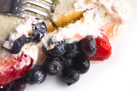usefulness: Appetizing fruit cake made of biscuit dough with a delicious sweet cream on which fresh strawberries and blueberries are laid melts in the mouth causing real pleasure Stock Photo