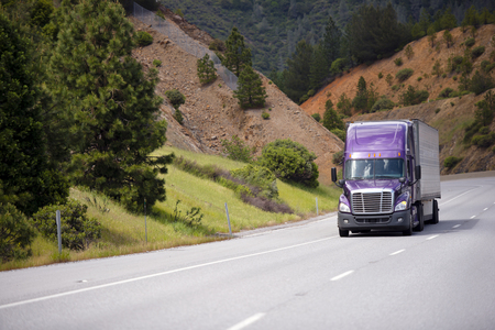 Lilac semi truck with aluminum trailer is moving along winding highway through the Grand pass in California against the background of orange sandstone mountain slopes and contrast green trees and small bushes and transporting commercial cargo to destinati