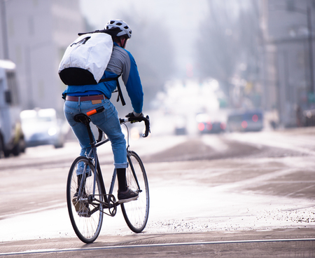 A man in jeans and sneakers in a protective helmet and with a backpack behind his shoulders enjoys riding a road bike through the streets of a modern urban city, in which there is a place for bikers - enthusiasts of a healthy lifestyle