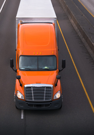 Orange semi truck with chrome grille and high roof move on the road with dry van trailer carry commercial goods and transporting cargo to long haul distanses all across America