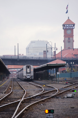 Passenger train stands on the curved railroad at historic railway station with awnings in Portland Oregon in little foggy weather Stock Photo