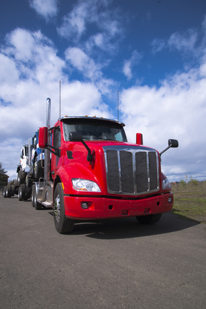A powerful modern big rig red semi truck carries other articulated lorry semi trucks of various models and colors, loaded one on top of another against a fantastic cloudy sky