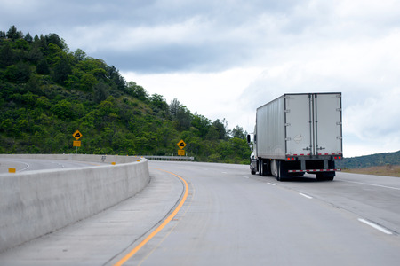 road surface: The modern classic way of transporting and delivering goods in America is reliable road transport with the help of powerful professional semi trucks with capacious and safe semi trailers on the developed network of American roads Stock Photo