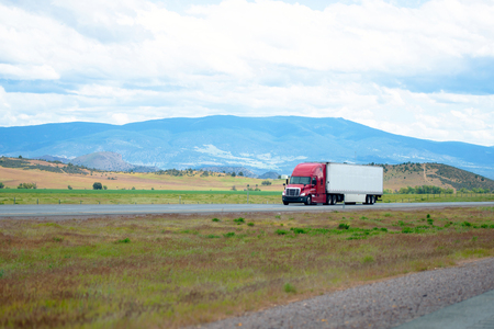 Red big rig semi-truck with white reefer trailer move on straight divided interstate highway I-5 in California with mountains on background