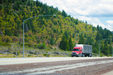 Red big rig modern shiny semi-truck with black tarp dry van trailer with aerodynamic spoiler in front of trailer move on straight divided interstate highway I-5 in Oregon with green trees forest on the background