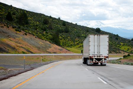 ドライバン トレーラー長距離貨物用の大きなリグトラックを半分割高速道路沿道の丘の上の緑の木々 を巻きオンします。