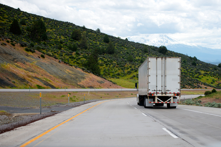 A big rig semi truck with a dry van trailer for long haul freight turn on winding dividing highway with green trees on roadside hills