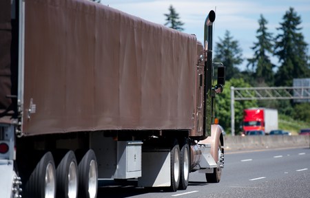 A classic big rig semi truck of soft beige color with high vertical chrome exhaust pipes and a trailer with a frame covered with a dense rubberized brown cloth moves forward along the bussy road
