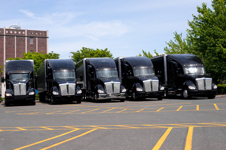 moving truck: Powerful stylish black big rig semi trucks with black semi trailers are lined up in an open parking lot awaiting for loading and transporting commercial cargo