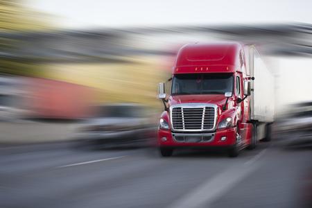 Roter moderner großer LKW der Rig-Hantel des professionellen Profikomforts halb mit Anhänger bewegen sich halb mit Ladung auf der Autobahn auf unscharfem Hintergrund