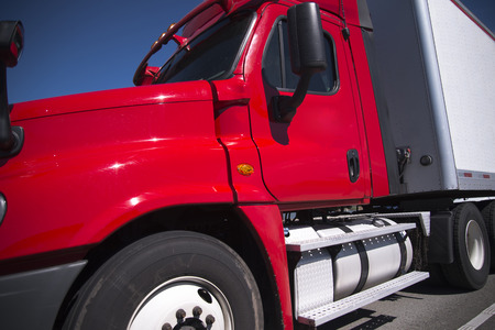 Bright red professional day cab modern big rig semi truck with dry van semi trailer for local delivery work move with cargo on the highway transporting it to destination warehouse