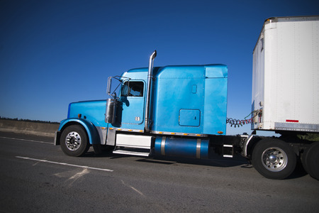 moving truck: Classic American model big rig semi truck in blue with long cab sleep compartment with semi trailer driving on wide highway on blue sky background