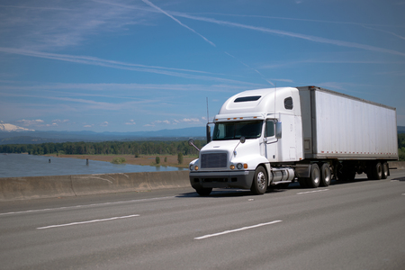 freightliner: Modern bonnet classic white big rig semi truck with dry van semi trailer – traditional bunch in trucking industry - driving by spectacular wide interstate highway delivering loaded cargo to destination
