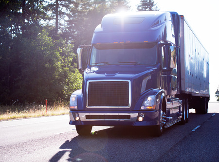 Popular model of modern dark blue big rig semi truck with dry van trailer transport cargo on the road with trees in sun ray light