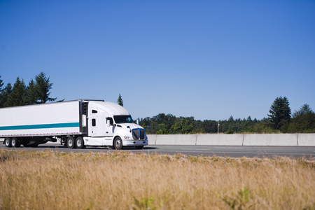 Modern white big rig semi truck tractor with high cab for comfort truck driver sleeping during the rest stop in long distance route carry temperature sensitive cargo in reefer semi trailer and running on flat straight highway with yellow grass on the shou